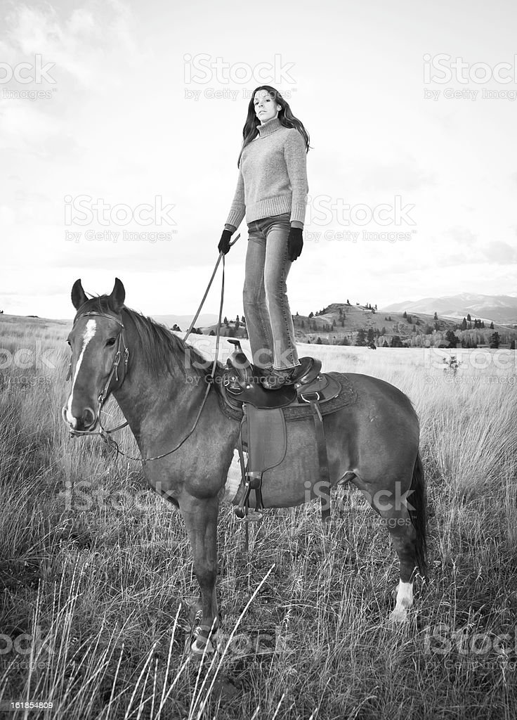 Woman standing on horse in field stock photo