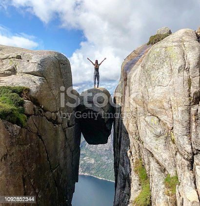 Woman standing on kjeragbolten mountain edge on Fjord in Norway summer 2018