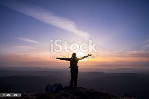 Rear view of silhouetted woman with arms outstretched standing on mountain during sunset.