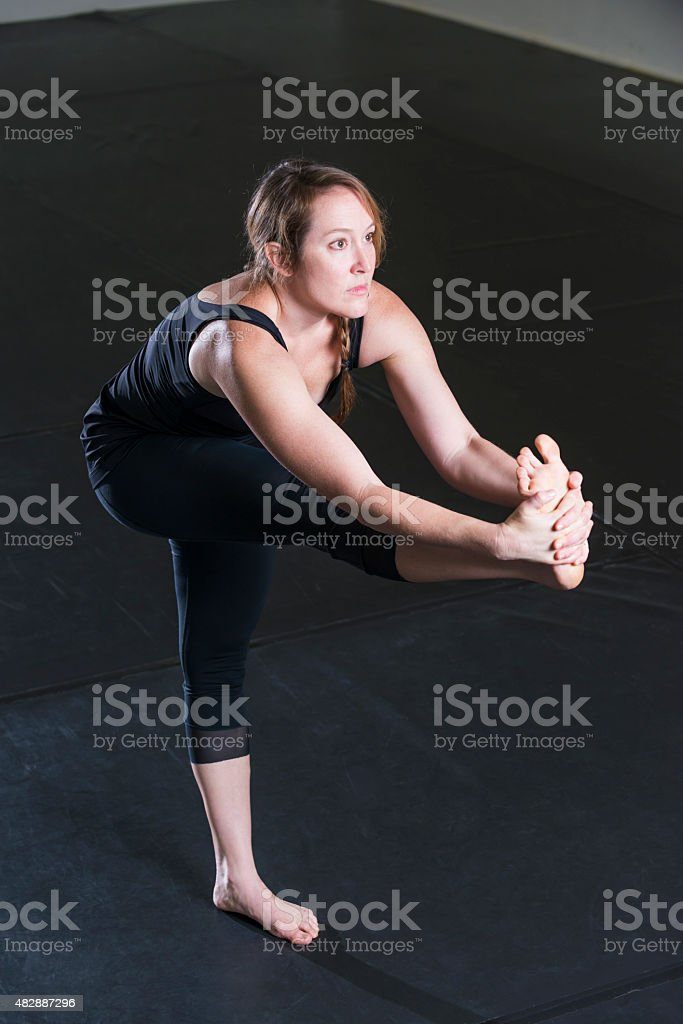 A woman in her 30s doing yoga. She is balancing on one leg, extending...