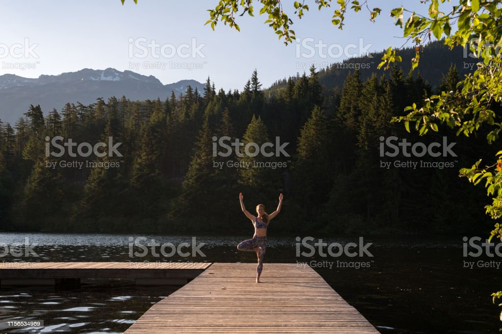 Full length of woman standing on one leg while exercising on pier....