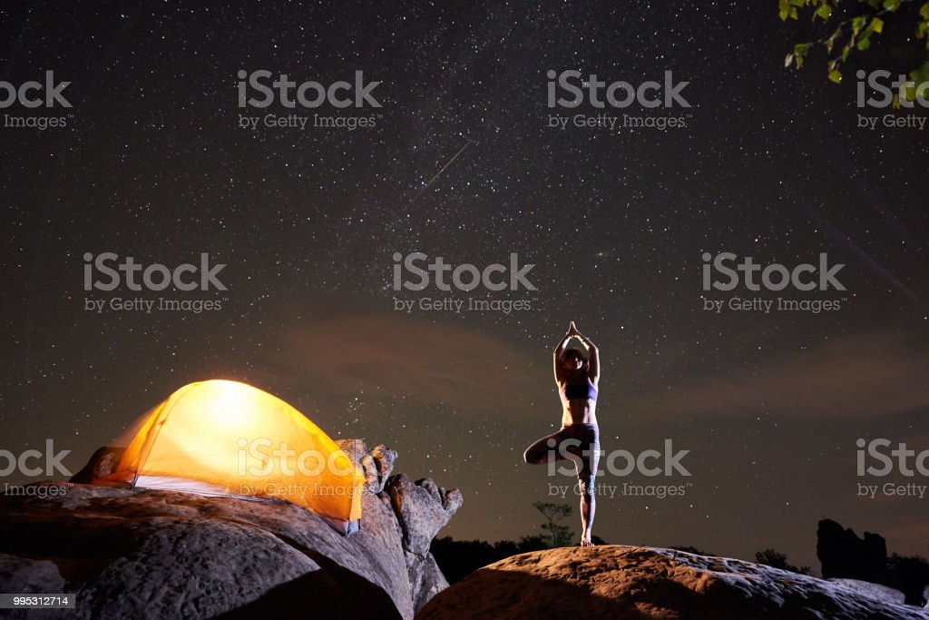 Brightly lit tourist tent and young slim woman standing on one leg...