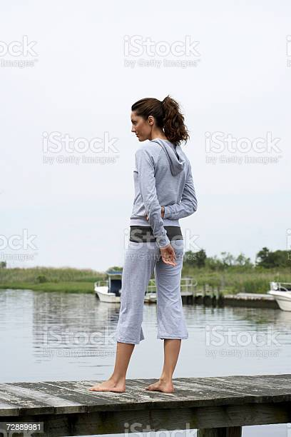 Woman Standing On Pier Stock Photo - Download Image Now
