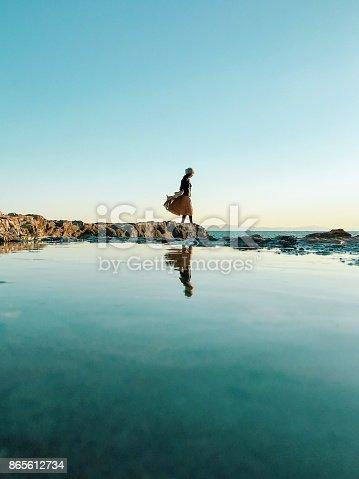 Woman standing on rock beside sea