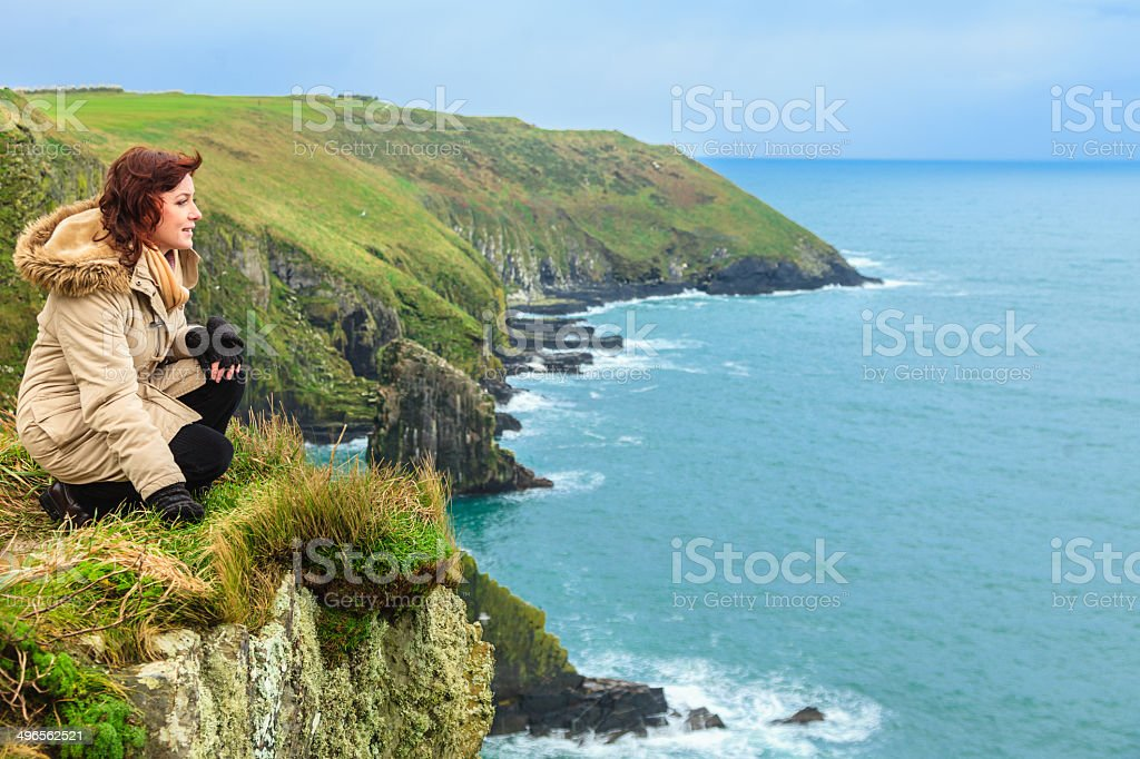 Woman standing on rock cliff by ocean Co. Cork Ireland stock photo