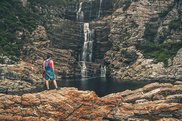 Woman standing on rock watching the waterfall of Tsitsikamma. Woman standing on rock watching the waterfall of Tsitsikamma National Park. Eastern Cape. South Africa. western cape province stock pictures, royalty-free photos & images
