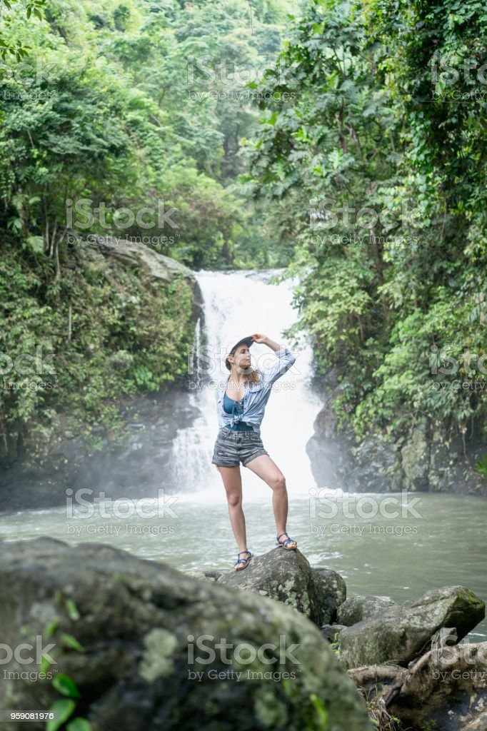 woman standing on rock with Aling-Aling waterfall and green plants on...