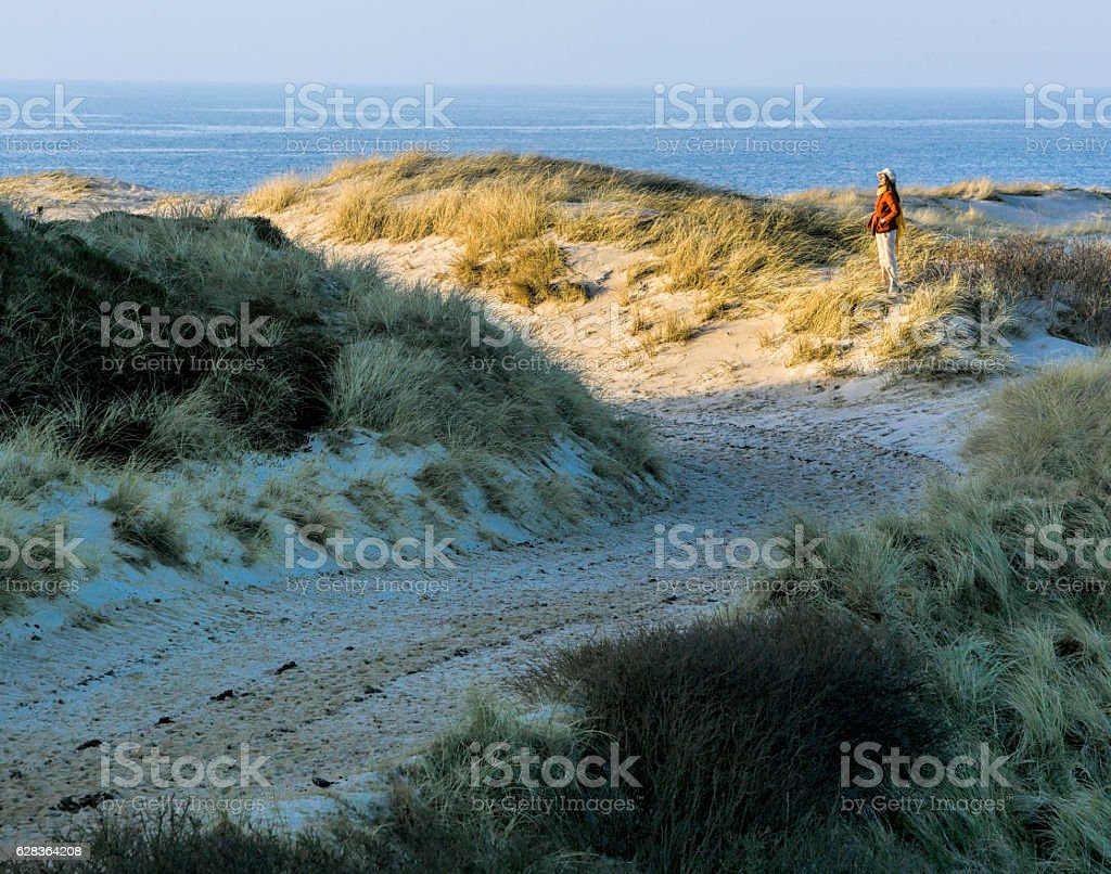 Woman standing on sand dune at beach of Sylt, Germany stock photo