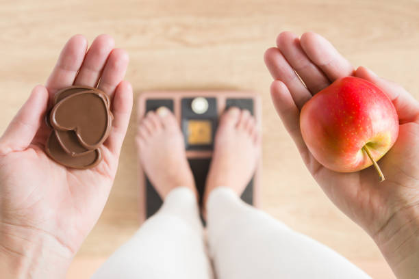 Woman standing on scales and holding apple and chocolate hearts. New start for healthy nutrition, body slimming, weight loss. Cares about body. Dilemma between fruits or sweets. Decision concept. Woman standing on scales and holding apple and chocolate hearts. New start for healthy nutrition, body slimming, weight loss. Cares about body. Dilemma between fruits or sweets. Decision concept. weight stock pictures, royalty-free photos & images