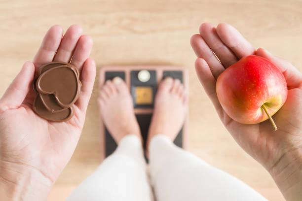 frau stehend auf skalen und apfel und schokolade herzen halten. neuer start für gesunde ernährung, körper schlank, gewichtsverlust. kümmert sich um körper. dilemma zwischen obst oder süßigkeiten. entscheidung-konzept. - fett nährstoff stock-fotos und bilder