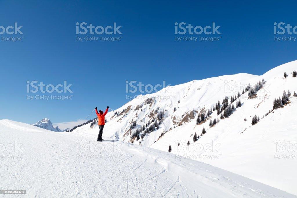 Frau stehend auf dem überdachten Schneeberg mit erhobenen Armen – Foto