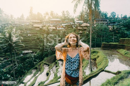 Young Caucasian woman on Tegallalang rice field in Bali, Indonesia with her hands up