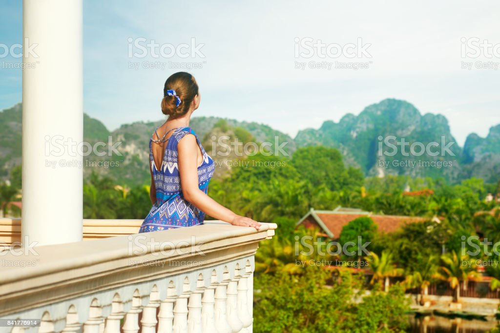 Woman standing on the balcony watching beautiful mountains view. stock photo