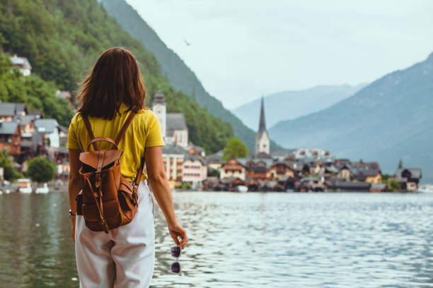 woman standing on the beach looking at hallstatt city copy space stock photo