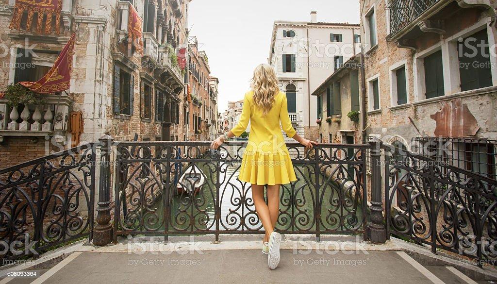 Woman standing on the bridge in Venice stock photo