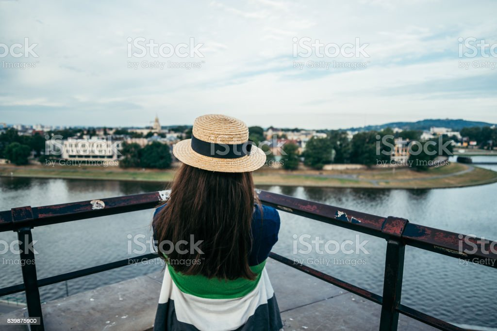woman standing on the pier in the city and looking on the river stock photo