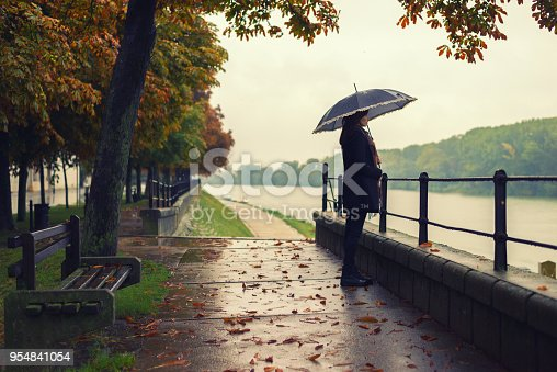 Woman with umbrella standing on the autumn rain.