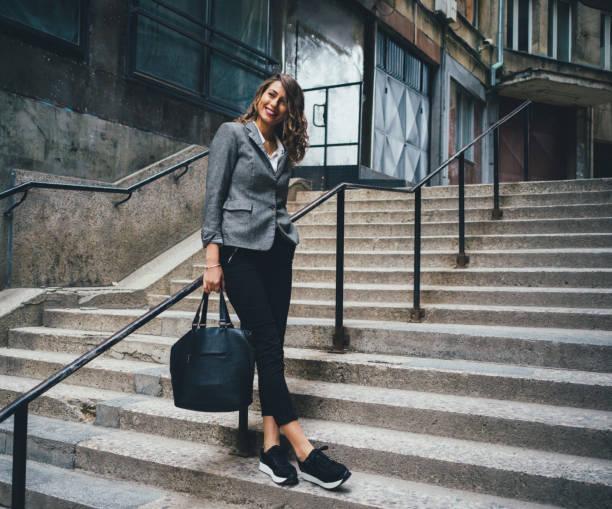 frau, stehend auf der treppe - modisch leger frauen stock-fotos und bilder