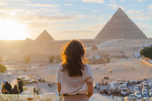 Young Caucasian woman standing on the  terrace on the  background of Giza pyramids