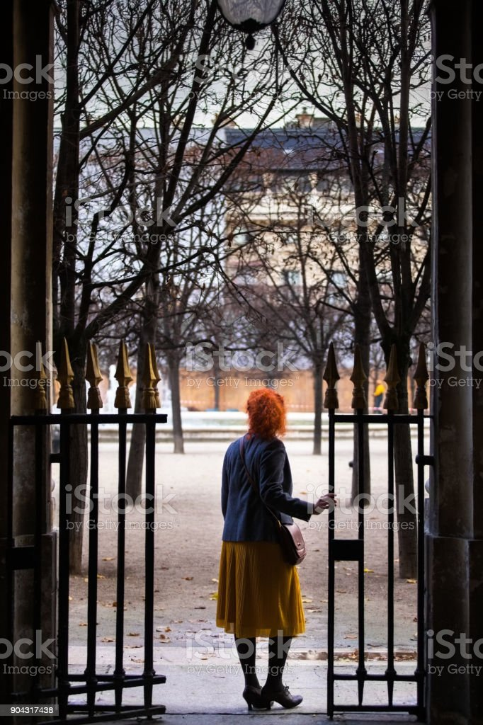 Woman Standing on Threshold Looking Through Wrought Iron Gate stock photo