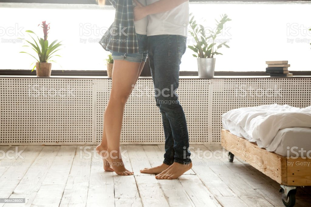 Woman standing on tiptoe hugging man, close up of legs - Royalty-free Adult Stock Photo