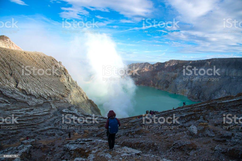 Woman standing on top of crater Mount Kawah Ijen volcano stock photo