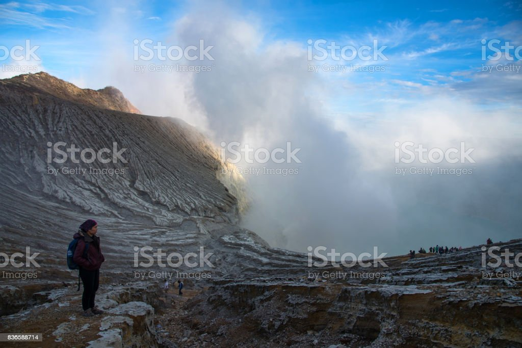 Woman standing on top of crater Mount Kawah Ijen volcano. stock photo