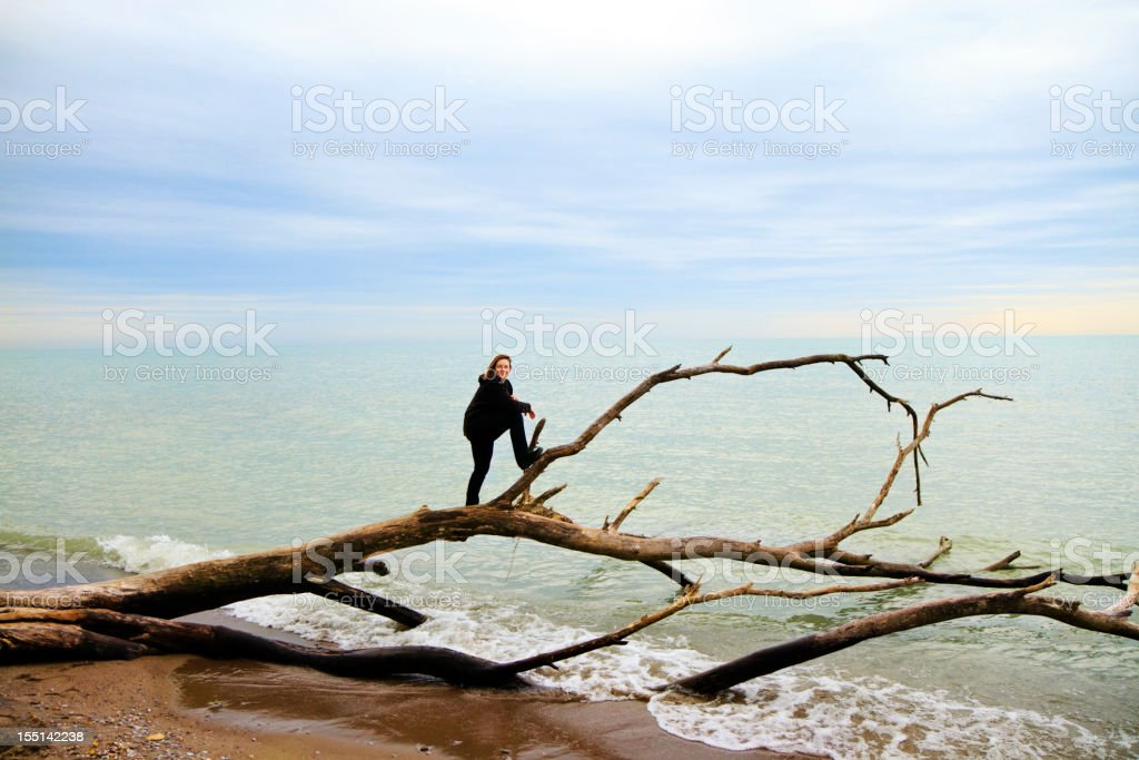 Woman Standing On Tree By The Water royalty-free stock photo