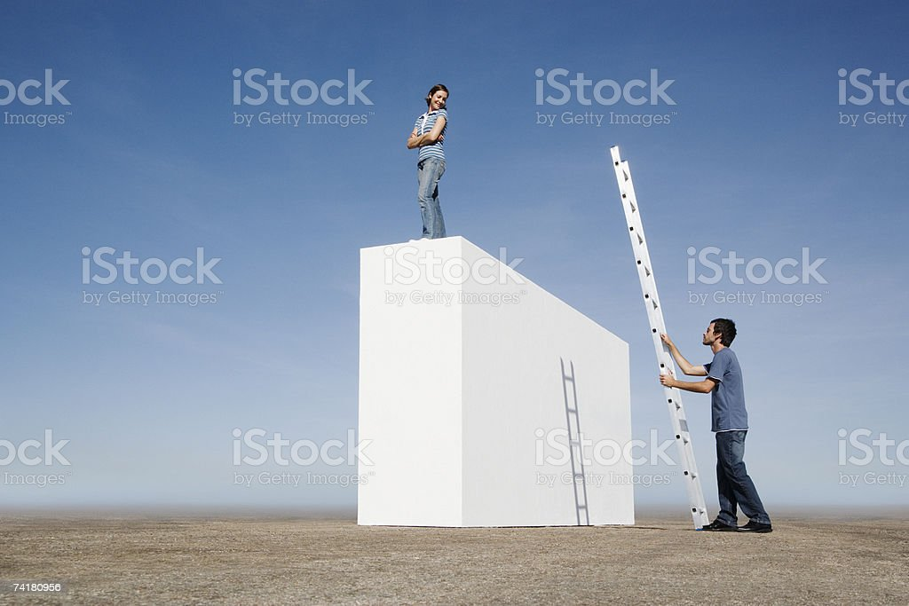 Woman standing on wall and man with ladder outdoors royalty-free stock photo