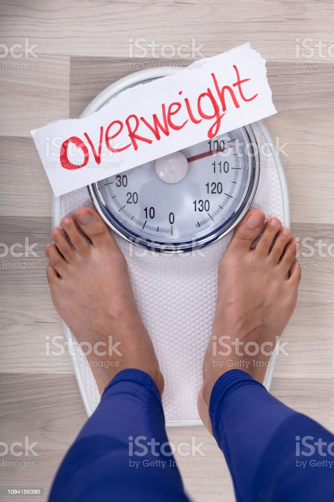 Close-up Of Woman\'s Feet On Weighing Scale Indicating Overweight On...