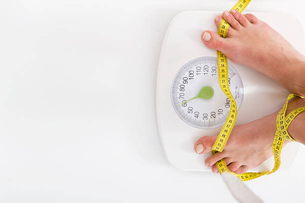 Woman standing on weight scale Woman standing on weight scale, canon 1Ds mark III weight stand stock pictures, royalty-free photos & images