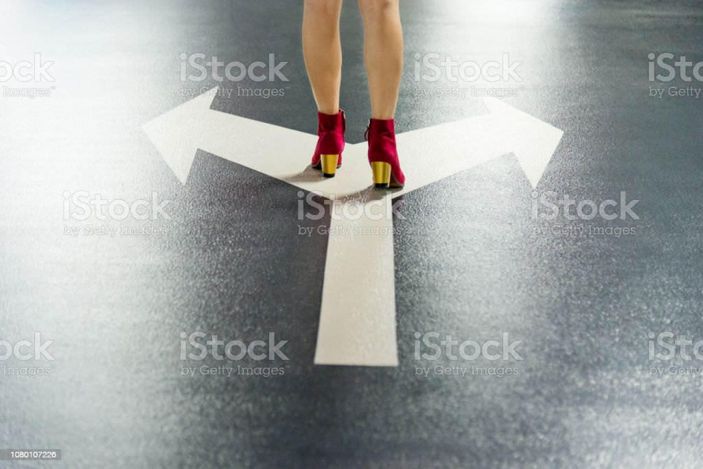 Woman standing on white direction arrow stock photo