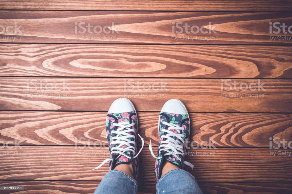 Woman standing on wooden floor in sneakers with floral pattern stock photo