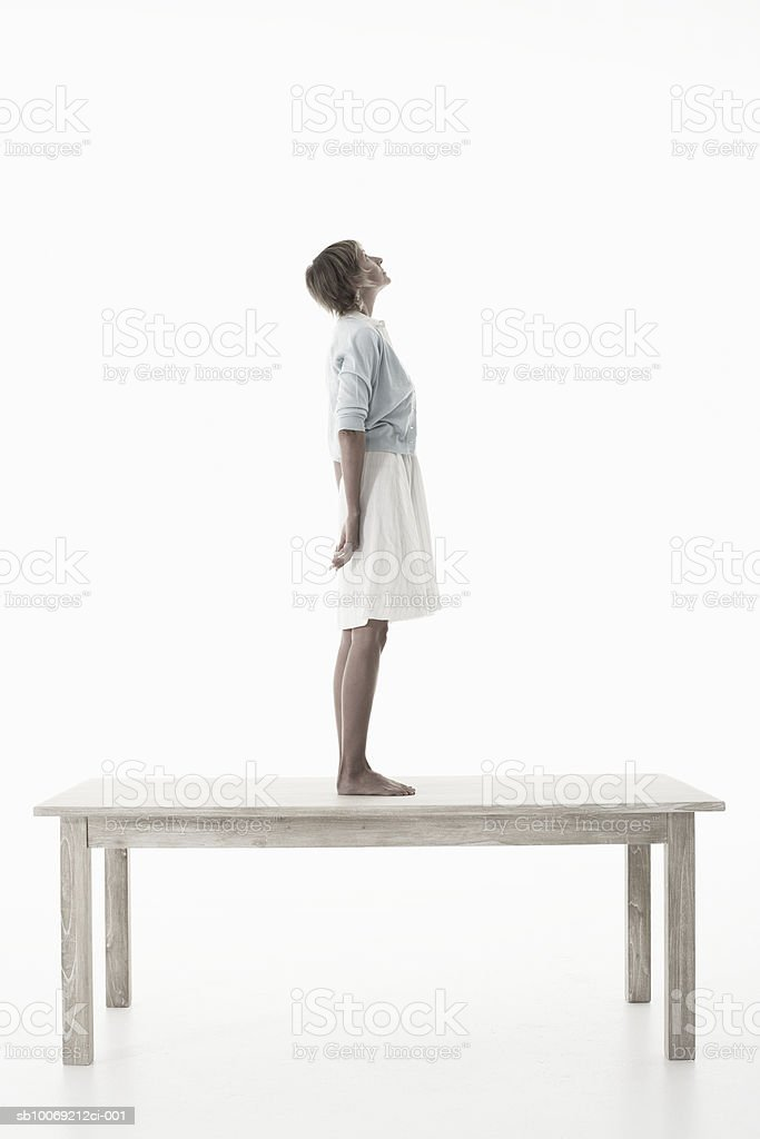 Woman standing on wooden table against white background, side view royalty-free stock photo