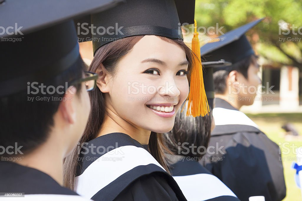 Woman standing out from a graduation group smiling stock photo