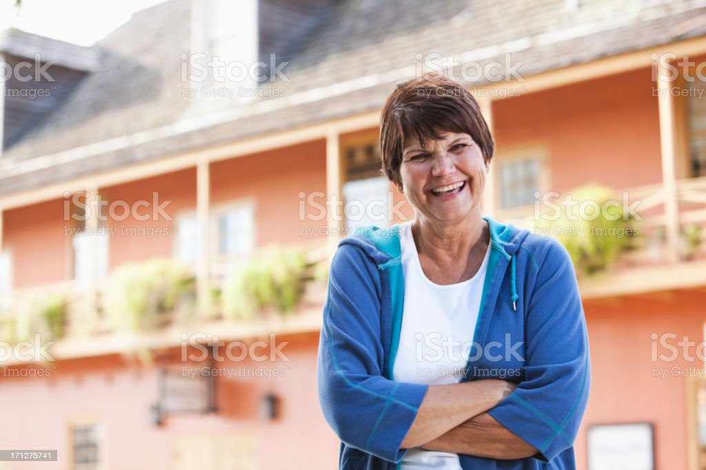 Woman standing outside building in sweatshirt stock photo