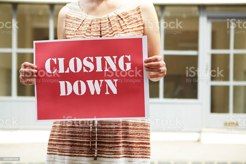 Woman Standing Outside Empty Shop Holding Closing Down Sign stock photo