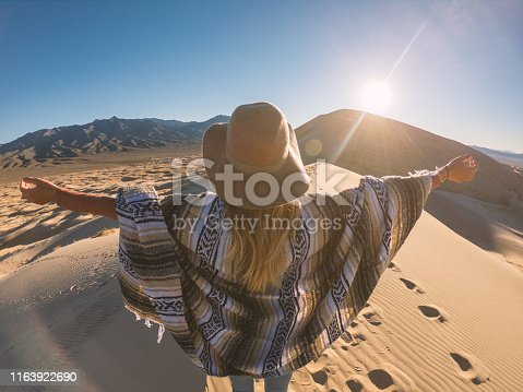 Distant unrecognisable woman standing sand dunes arms outstretched enjoying freedom in nature; girl hiking arms open on top of mountain