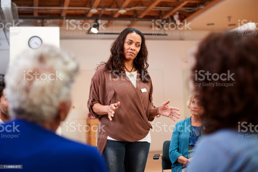 Woman Standing To Address Self Help Therapy Group Meeting In...