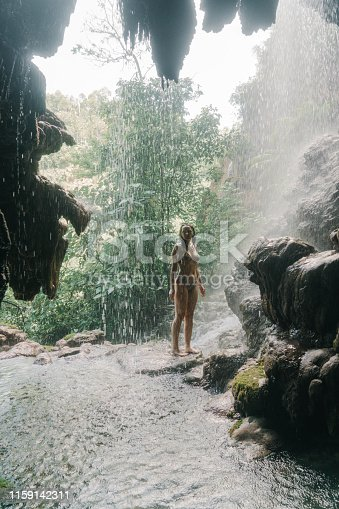Young Caucasian woman  standing under the flowing waterfall on Java, Indonesia