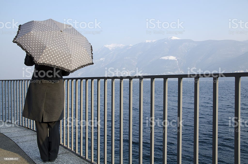 Woman standing up on the lakefront with a umbrella royalty-free stock photo
