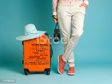 A young woman standing with a an orange suitcase beside her. She is wearing a cream colored pants and red tennis shoes with white soles. She is holding a twin lens reflex camera in right hand. Her left leg is crossed over her left leg. The woman's body is only visible from the waist down. Image taken in studio over blue background.