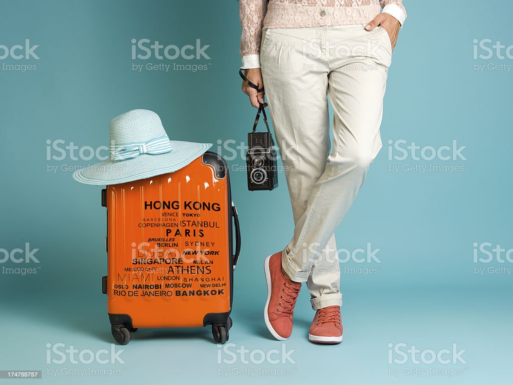 Woman standing with a suitcase beside her stock photo