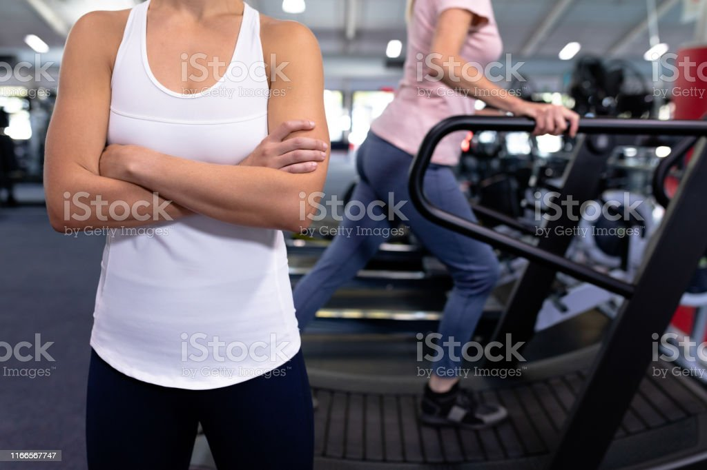 Mid section of woman standing with arm crossed in modern sports...