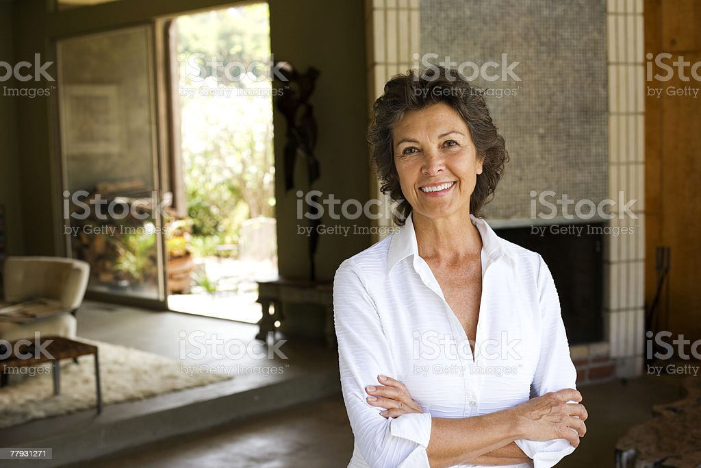 Woman standing with arms crossed smiling in modern home stock photo