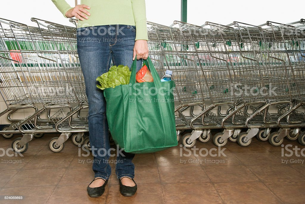Woman Standing with Canvas Grocery Bag stock photo