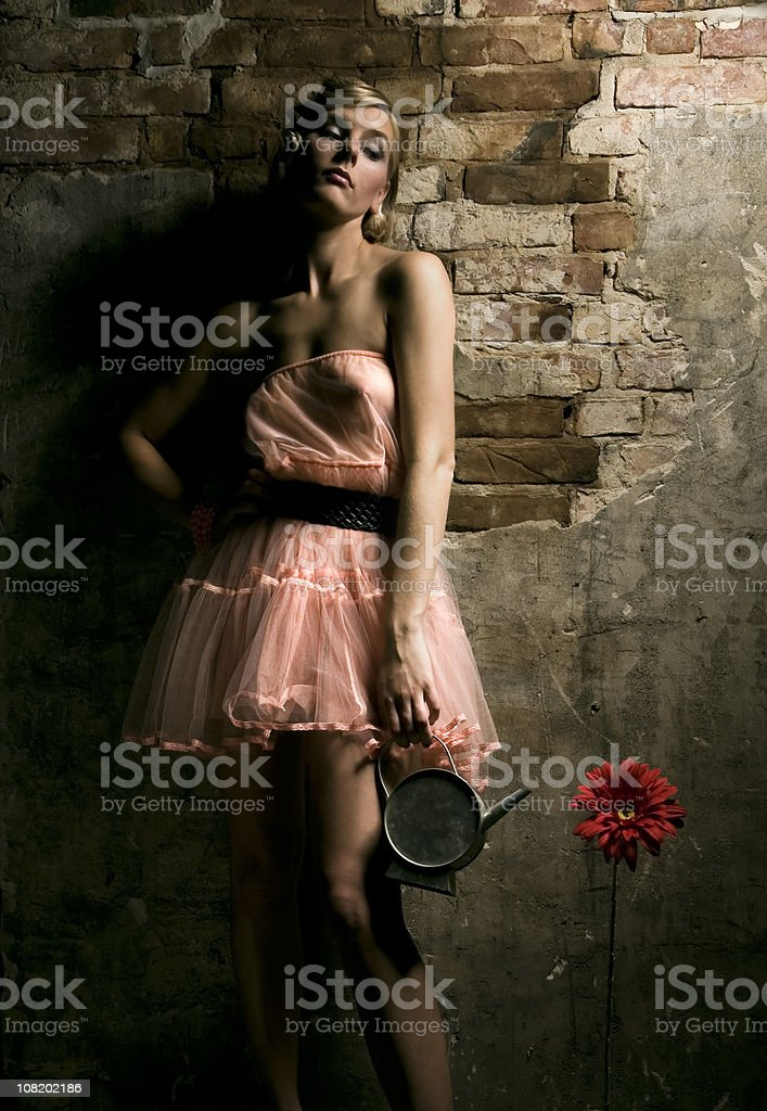 Woman Standing with Flower and Watering Can Indoors royalty-free stock photo