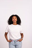 Beautiful young woman standing with hands in the pocket, looking at camera with a serious facial expression. The woman with a natural look, no makeup at all, wearing white t-shirt and jeans. Waist up portrait of elated beautiful African female model on white background.