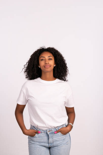 Woman standing with hands in the pockets. Beautiful young woman standing with hands in the pocket, looking at camera with a serious facial expression. The woman with a natural look, no makeup at all, wearing white t-shirt and jeans. Waist up portrait of elated beautiful African female model on white background. white t shirt stock pictures, royalty-free photos & images