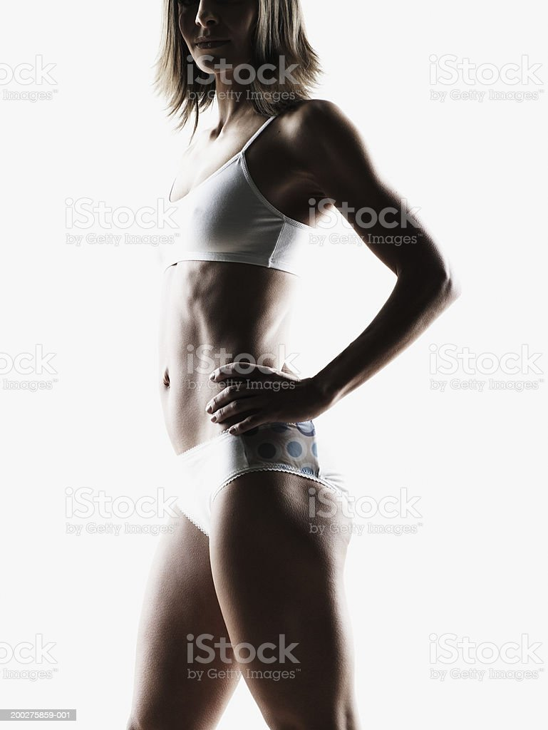 Woman standing with hands on hip, wearing underwear, side view royalty-free stock photo